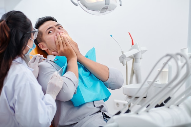 Frightened young vietnamese man covering mouth and looking at dentist with small mirror and carver