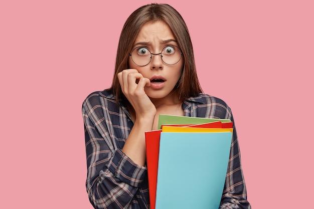 Giovane donna spaventata in posa contro il muro rosa con gli occhiali