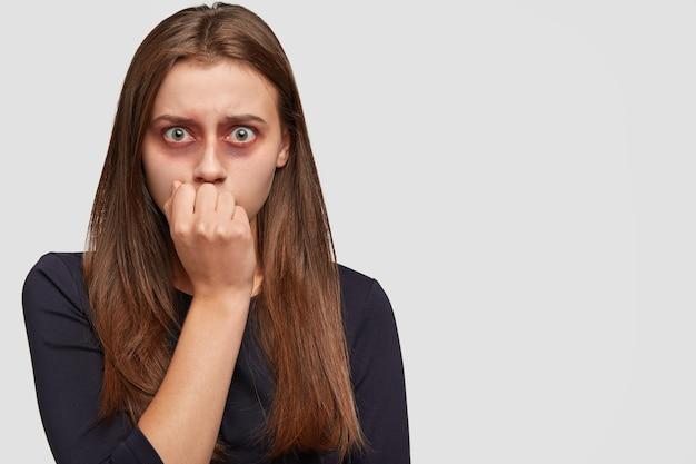 Испуганная молодая женщина с синяками позирует на белой стене