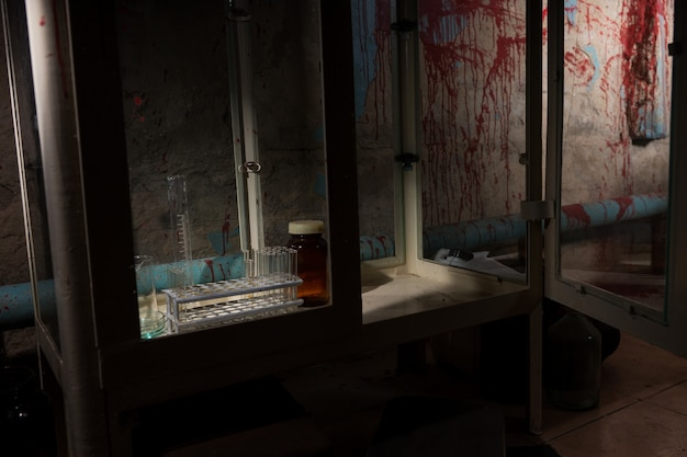 Frightening halloween theme blood of stained laboratory with test tubes holder and other medicine devices inside with blood spattered wall in dark room