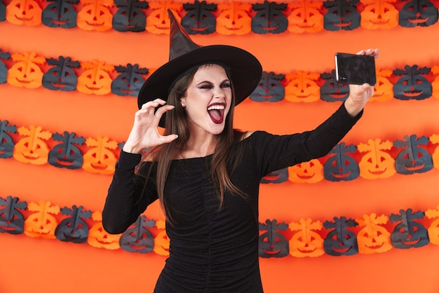Frightening witch girl in black halloween costume taking selfie photo on smartphone isolated over orange pumpkin wall