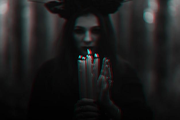 무서운 마녀는 촛불로 신비로운 의식을 수행합니다. 3d 글리치 가상 현실 효과가 있는 흑백
