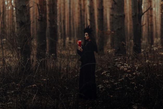 무서운 마녀는 우울한 어두운 숲에서 양초로 신비로운 의식을 수행합니다