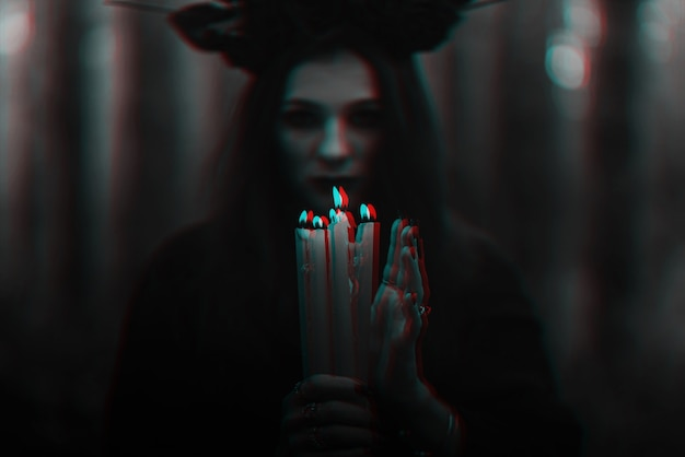 Frightening witch performs an occult ritual with candles. black and white with 3d glitch virtual reality effect