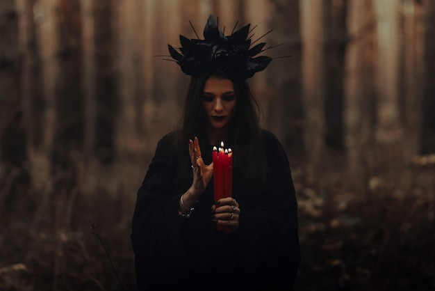 Frightening witch performs an occult ritual with candles in a gloomy dark forest