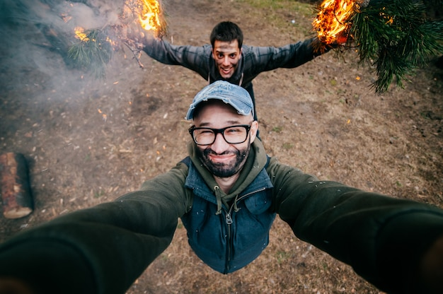 Frineds make selfie. crazy funny boys mess around. men at nature playing and fooling with fire. eccentric bizarre strange unusual young guys with dirty faces mad party in forest. burn, flame, smoke.
