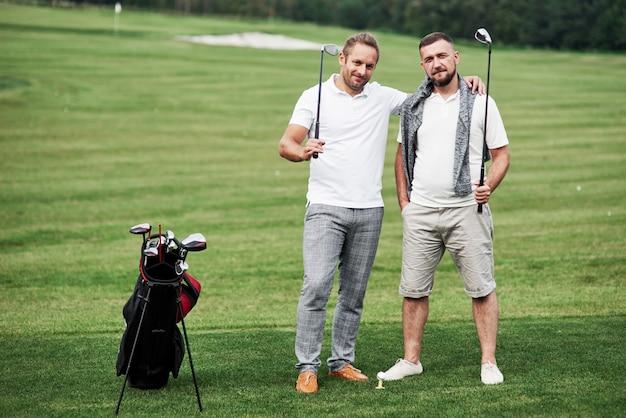아름 다운 녹색 잔디에 서있는 두 골퍼 사이의 우정. 프리미엄 사진