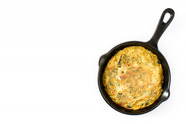 Frittata made of eggs and vegetables in a iron pan, isolated on white surface top view copy space