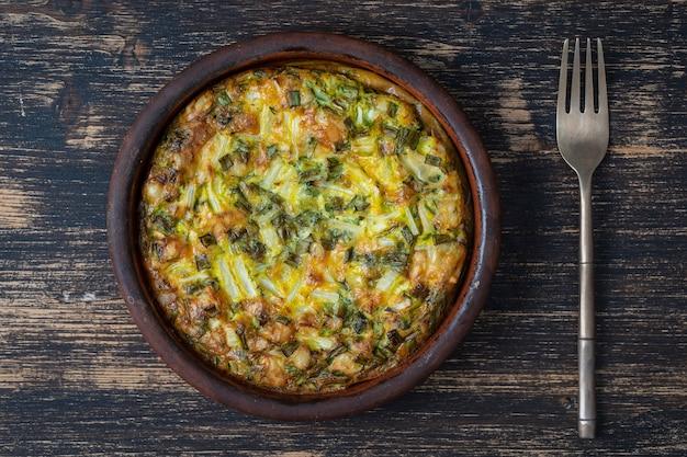 古い木製のテーブルの上にフォークと卵、コショウ、ネギ、チーズのフリッタータ