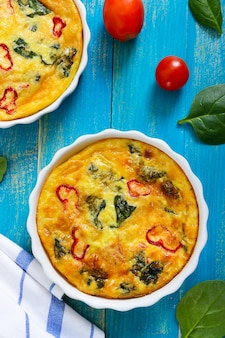 新鮮な野菜とほうれん草のフリッタータ。青い木製の背景にセラミックの形でイタリアのオムレツ。上面図。