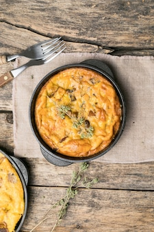 木製の背景の鍋にキノコとフリッタータ。フリッタータはイタリアの朝食料理です。