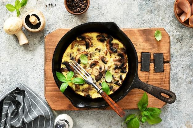 コンクリートの背景にバジルと鍋にキノコとフリッタータ。フリッタータはイタリアの朝食料理です。