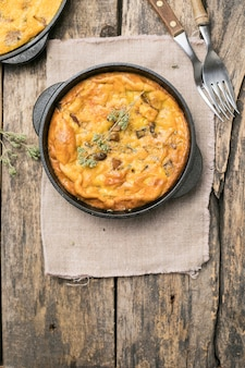 Frittata with mushrooms in a pan on wooden background. fritata is an italian breakfast dish.