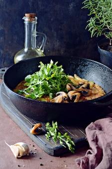 Фриттата с картофелем, грибами, рукколой и зеленью на завтрак на темном фоне.