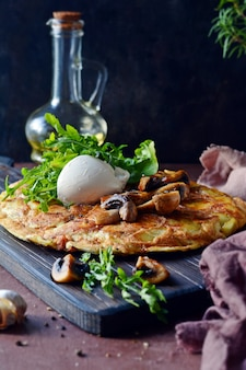 Frittata with potatoes, mushrooms, arugula and herbs for breakfast on a dark background.