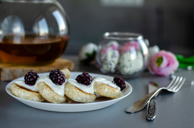 Fritters of cottage cheese with blackberries and sour cream for healthy breakfast.
