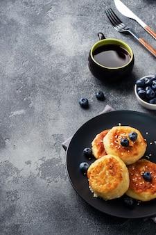ブルーベリーとカッテージチーズのフリッター。チーズカードチーズケーキ、暗いコンクリートのテーブルでパンケーキ。コピースペース。
