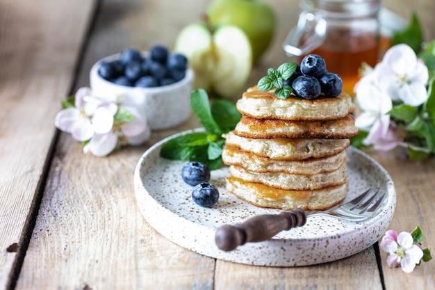 リンゴと木製のテーブルの上に蜂蜜とフリッター。秋の朝食。