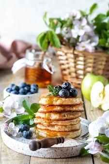 リンゴと木製のテーブルの上に蜂蜜とフリッター。