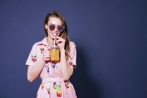 Красивая женщина в красочном платье с напечатанными friuts, позирующими со стаканом сока