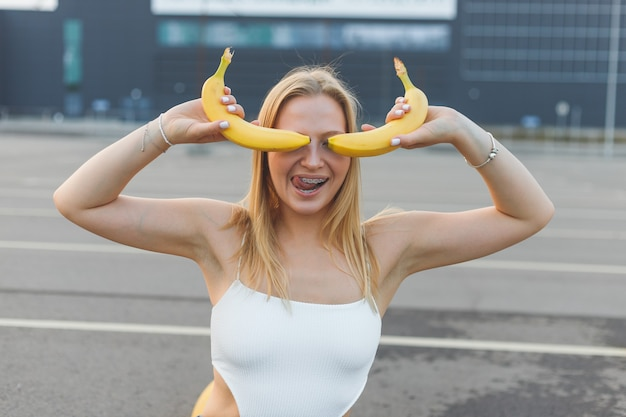 Frivolously and mischievous young woman with braces on teeth holding bananas on her face has fun out...