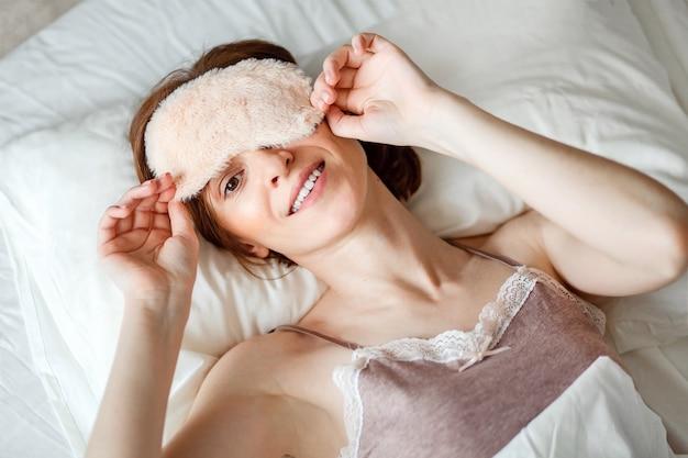 Сверху снимается вид здоровой молодой женщины, которая смеется и снимает с себя спящую маску после спокойного ночного отдыха.
