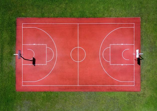 푸른 잔디로 둘러싸인 흰색 표시와 후프가 있는 빈 빨간색 농구 경기장의 공중 전망