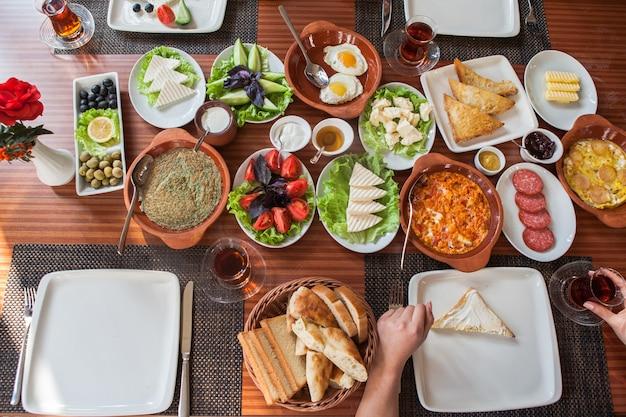 Сверху ассорти завтрак с омлетом и стаканом чая и человеческая рука в сервировочных салфетках