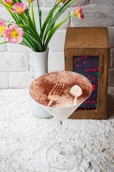 Сверху капучино с надписью с вазой с цветами и салфетницей в бокале для коктейля