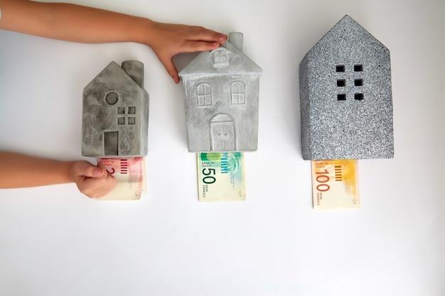 Сверху креативная композиция из маленьких и больших домов с разной ценой в новых израильских шекелях.