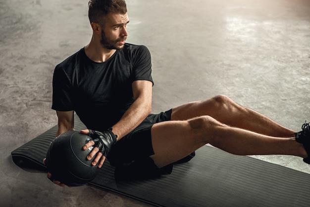Сверху решительный спортсмен делает упражнения на пресс с мячом на коврике во время фитнес-тренировки в тренажерном зале