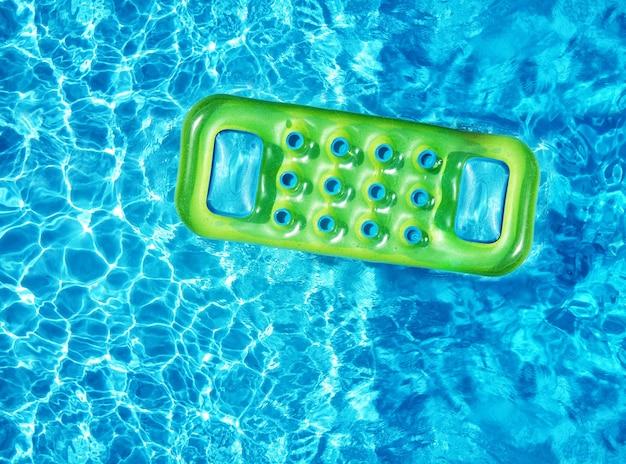 여름철 햇빛 아래 수영장의 푸른 수면에 떠 있는 밝은 녹색 팽창식 매트리스의 드론 보기