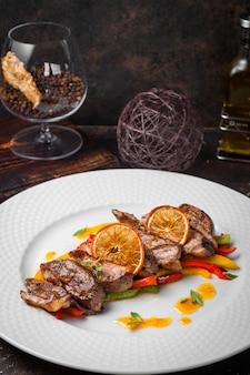Сверху жареное мясо с жареными овощами и бокалом апельсина и бренди в белой тарелке