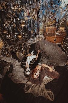 上から神秘的なインテリアのスタジオの床に横たわっているハロウィーンのカップル。ホリデーメイクの男女