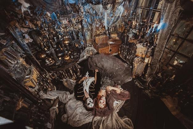위에서 할로윈 커플은 신비로운 인테리어가 있는 스튜디오 바닥에 누워 있습니다. 휴일 화장에 남자와 여자