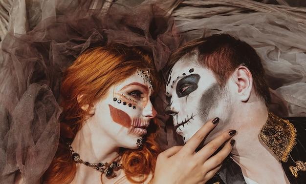 上から神秘的なインテリアのスタジオの床に横たわっているハロウィーンのカップル。ホリデーメイクの男女。閉じる