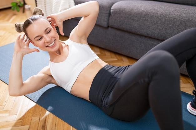 上から、自宅でのフィットネストレーニング中にソファの近くのマットで腹部のクランチをしている頭の後ろに手を持っている幸せな女性アスリート