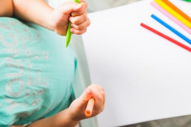 Сверху ребенок с карандашами