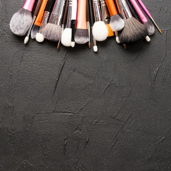 From above makeup brushes on black