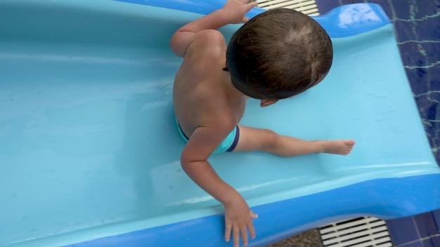 Сверху малыш в плавках катается по синей горке в бассейне