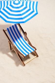 우산 아래 줄무늬 의자가있는 해변 라운지 공간 위에서.