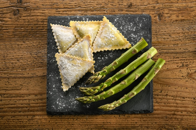 生の伝統的なイタリアの三角形のラビオリパスタの上から、木製のテーブルに置かれた小麦粉をまぶしたスレートボードに新鮮なグリーンアスパラガスを添えて