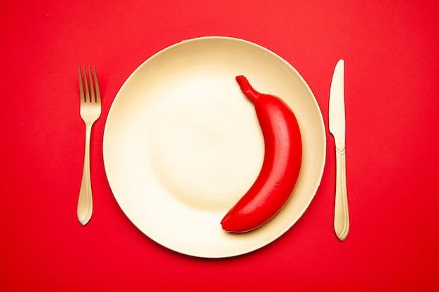 Сверху вкусный сырой цельный красный банан, подаваемый на белой тарелке с вилкой и ножом
