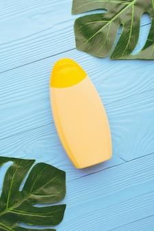 青い木に緑のモンステラの葉で構成された化粧品またはクリーム用の黄色いボトルの上から。