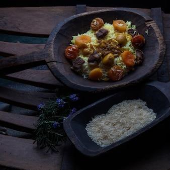 Сверху плов с мясом и сушеными фруктами и каштаном и рисом в деревянной тарелке