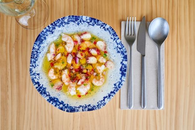 신선한 해산물 샐러드 한 접시, 화이트 와인 한 잔이 있는 레스토랑 테이블 위