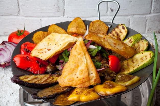 토마토와 양파, 파를 곁들인 sac 케밥 위에서