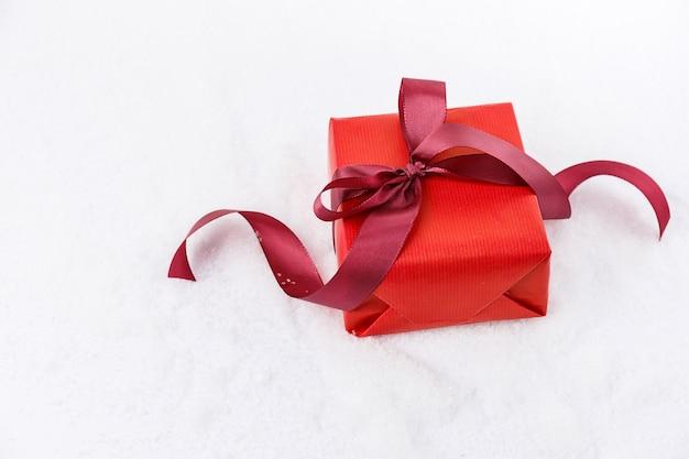 白い雪の上に横たわるリボンで飾られた明るいギフトボックスの上から