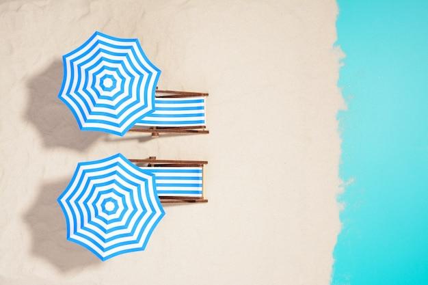 해변에서 우산 아래 스트라이프 의자의 총 위에서.