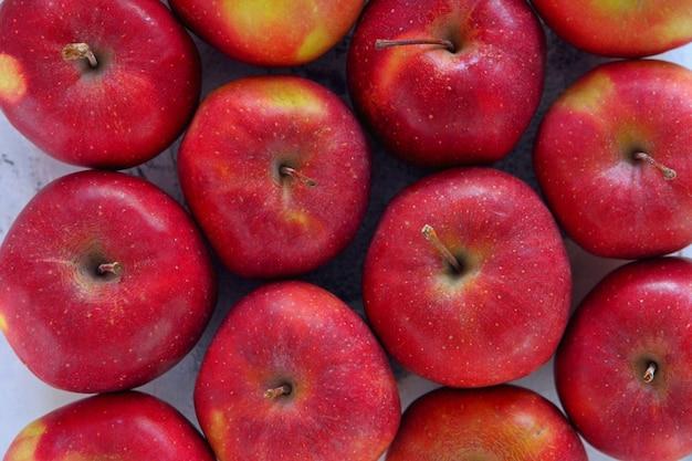Сверху лежали плоские вкусные красные яблоки. гирация красные спелые яблоки крупным планом.